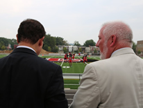 Mayor Vincent Gray and DGS Director Brian Hanlon watching the team practice on the new Dunbar Athletic Field