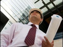photo of business man in hard hat carrying blueprints